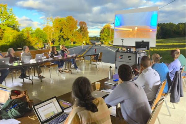 students in classroom surreally overlaid on rural landscape image