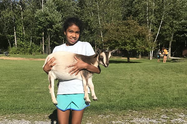 Young person holding a goat in an outdoor setting
