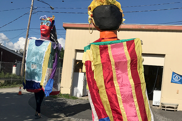 two figures in brightly colored costumes made of large boxes