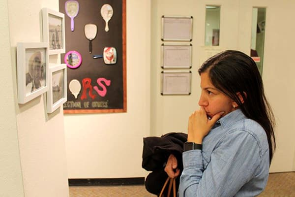 woman views framed images on a wall